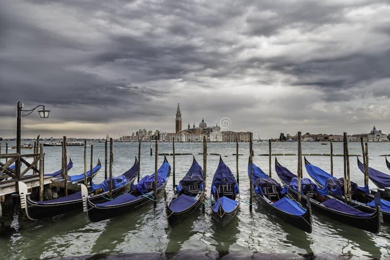 Δραματική άποψη της Βενετίας με τη σειρά των γονδολών που ελλιμενίζονται στους πόλους στοκ φωτογραφίες