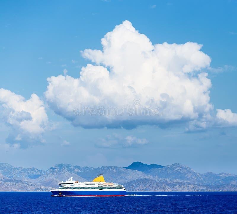 Δραματική άποψη του κρουαζιερόπλοιου με το ογκώδεις άσπρους σύννεφο και το μπλε ουρανό στοκ φωτογραφία