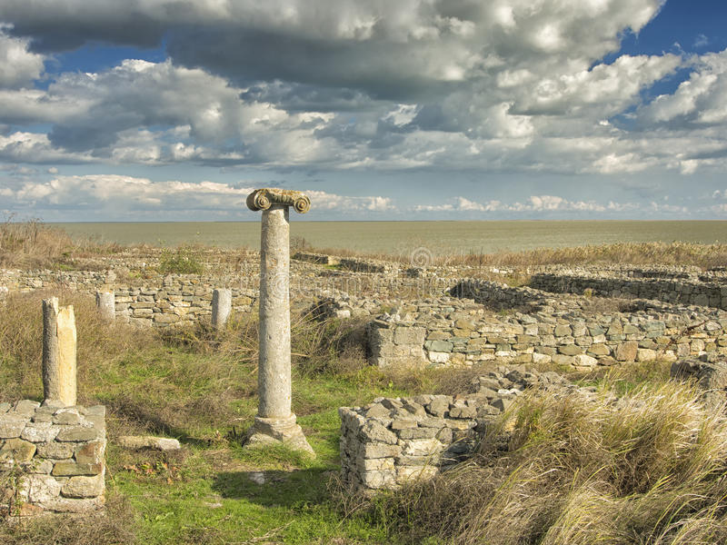 Δραματικός μπλε ουρανός με τα άσπρα σύννεφα πέρα από τις καταστροφές μιας στήλης αρχαίου Έλληνα σε Histria, στις ακτές Μαύρης Θάλ στοκ εικόνα με δικαίωμα ελεύθερης χρήσης