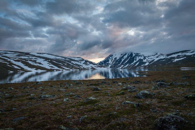 Δραματικός ουρανός με τα σύννεφα, τα βουνά και μια λίμνη στοκ εικόνες
