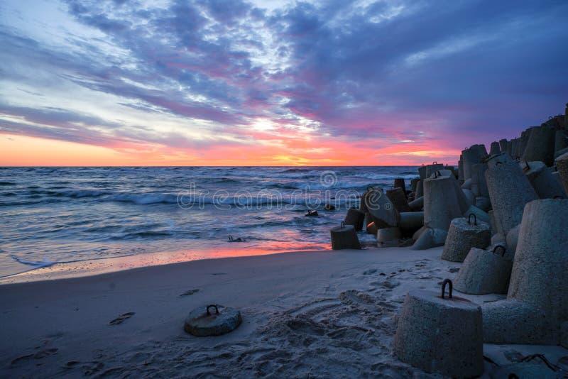 Δραματικό ηλιοβασίλεμα πέρα από τη θάλασσα της Βαλτικής σε μια κενή παραλία στοκ εικόνες