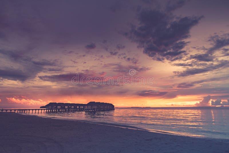 Δραματικό ηλιοβασίλεμα παραλίας, πολυτελείς υδροβάτες με υπερκατασκευασμένο ουρανό Μοτίβο τροπικού τοπίου, απαλά κύματα, ήρεμο πα στοκ εικόνα