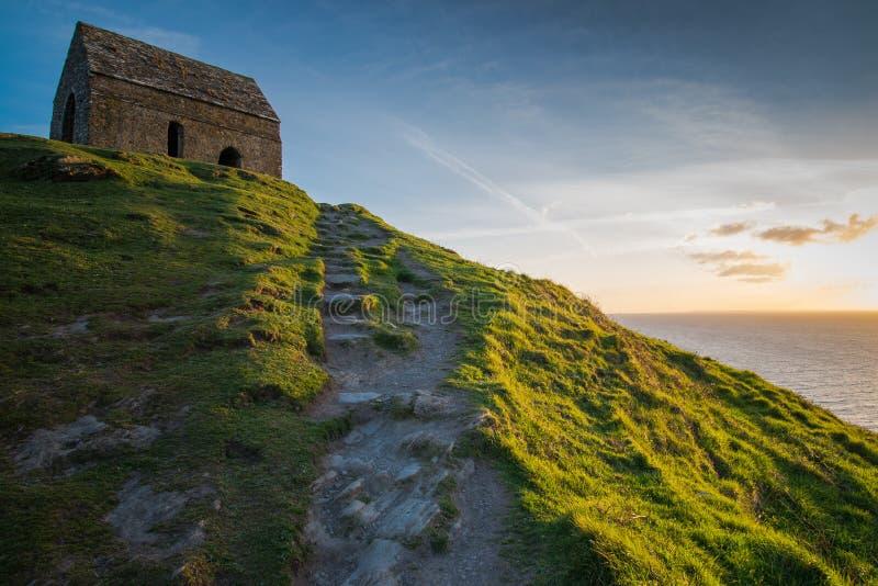 Δραματικό ηλιοβασίλεμα πέρα από το λόφο με το παρεκκλησι στη Cornish ακτή στοκ φωτογραφία