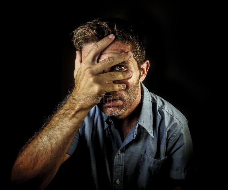 Δραματικό πορτρέτο του νέου ελκυστικού ατόμου που καλύπτει το πρόσωπο με τα χέρια αλλά τα δάχτυλα ανοίγματος για να δει και να κα στοκ φωτογραφίες