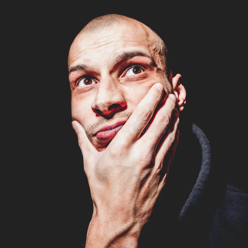Δραματικό στενό επάνω πορτρέτο του νέου φαλακρού ατόμου με το χέρι στο πρόσωπό του που φαίνεται επάνω μην απομονωμένου στο μαύρο  στοκ φωτογραφίες
