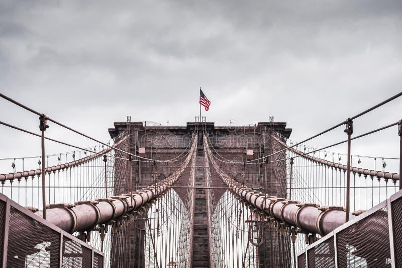 Δραματικό τοπίο Imerssive της αρχιτεκτονικής της διάσημης γέφυρας του Μπρούκλιν στη Νέα Υόρκη κάτω από έναν αντιπαραβαλλόμενο θυε στοκ φωτογραφίες