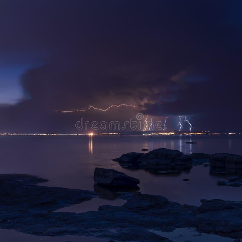 Δραματικό υπόβαθρο φύσης - βροντές στο σκοτεινό ουρανό πέρα από τη θάλασσα στοκ φωτογραφίες