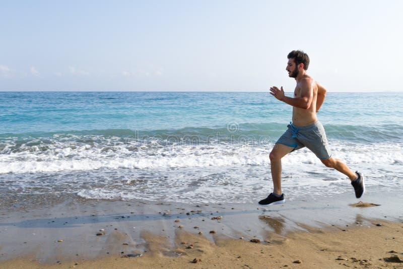 Δρομέας ατόμων που τρέχει γρήγορα στην υγρή άμμο που οργανώνεται στην παραλία στοκ φωτογραφία
