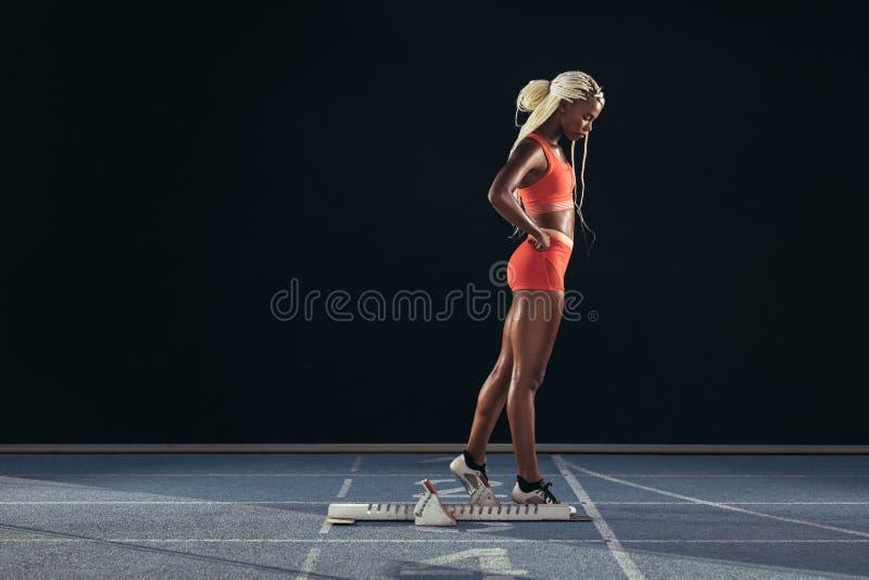 Δρομέας γυναικών που στέκεται σε μια τρέχοντας διαδρομή στοκ εικόνα