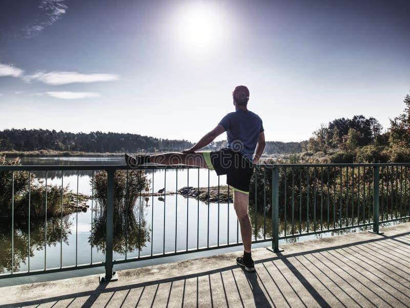 Δρομέας που κάνει την τεντώνοντας άσκηση στη γέφυρα Ένα ενεργό νευρικό άτομο στοκ φωτογραφίες
