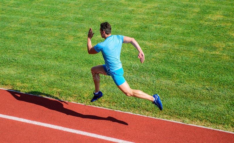 Δρομέας που συλλαμβάνεται στον αέρα Σύντομη τρέχοντας πρόκληση απόστασης Ταχύτητα ώθησης Υπόβαθρο χλόης διαδρομής τρεξίματος αθλη στοκ φωτογραφία