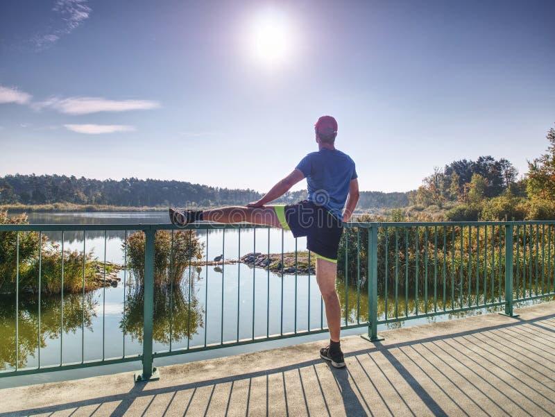 Δρομέας στο μαύρο leggings do τέντωμα σωμάτων στην πορεία γεφυρών στοκ εικόνα