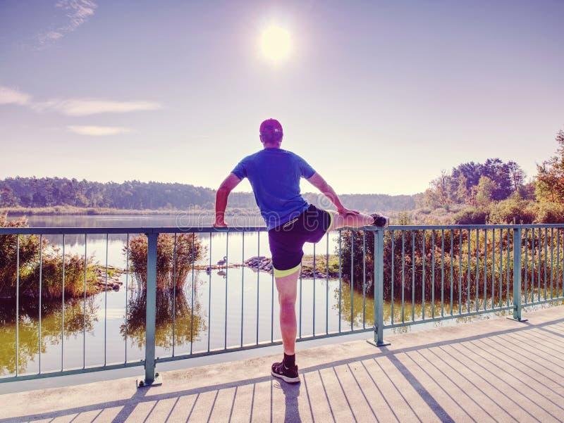 Δρομέας στο μαύρο leggings do τέντωμα σωμάτων στην πορεία γεφυρών στοκ φωτογραφία με δικαίωμα ελεύθερης χρήσης