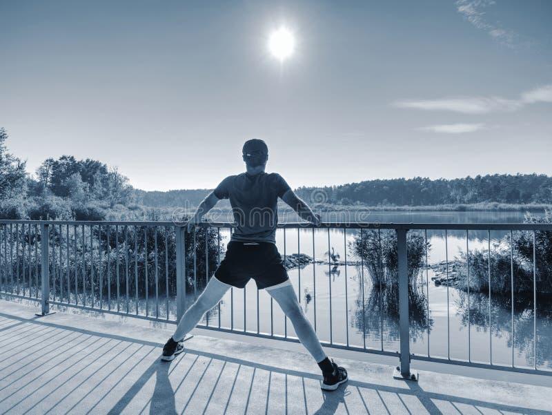Δρομέας στο μαύρο leggings do τέντωμα σωμάτων στην πορεία γεφυρών στοκ φωτογραφίες με δικαίωμα ελεύθερης χρήσης