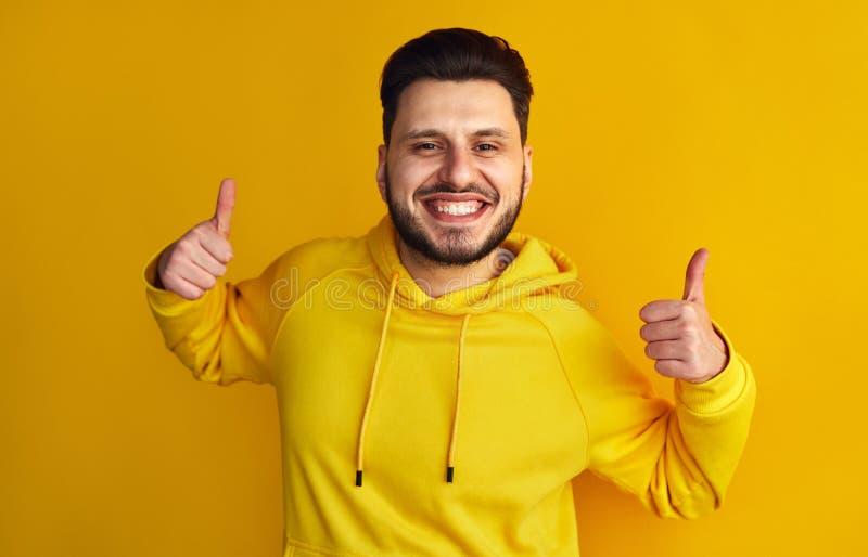 Δροσίστε το γενειοφόρο αρσενικό στο κίτρινο hoodie που χαμογελά και που παρουσιάζει αντίχειρα επάνω στη χειρονομία και με τα δύο  στοκ φωτογραφίες