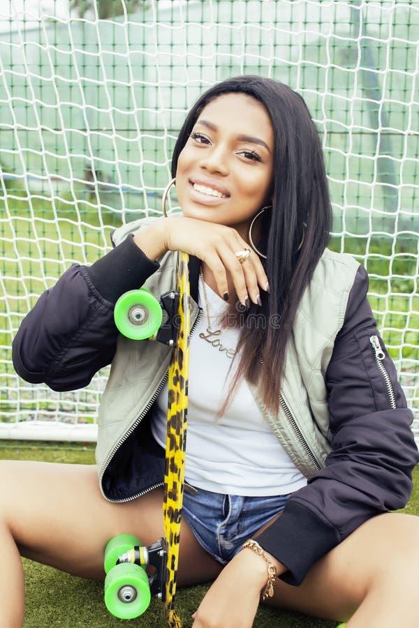 Δροσερή όμορφη χαμογελώντας αφροαμερικανίδα ευτυχής νέα γυναίκα με την ένωση πινάκων σαλαχιών γύρω στον τομέα foothball στοκ φωτογραφίες