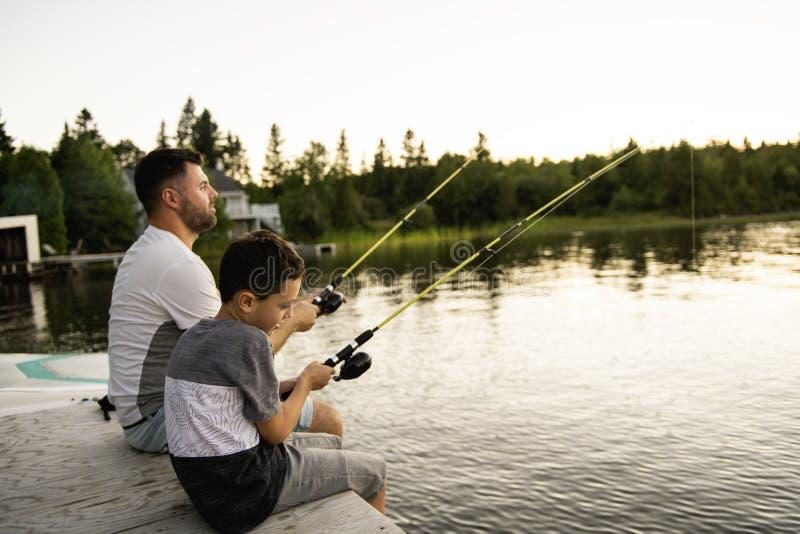 Δροσεροί μπαμπάς και γιος που αλιεύουν στη λίμνη στοκ εικόνες με δικαίωμα ελεύθερης χρήσης