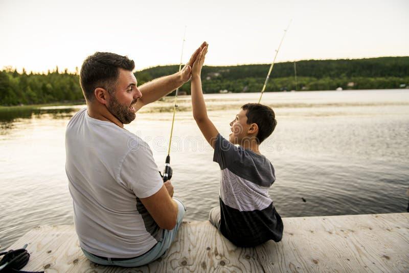 Δροσεροί μπαμπάς και γιος που αλιεύουν στη λίμνη στοκ φωτογραφία