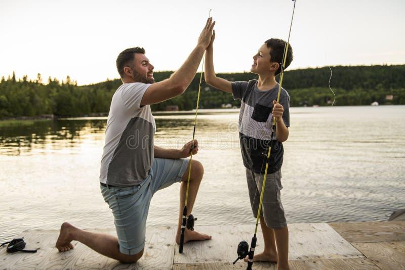 Δροσεροί μπαμπάς και γιος που αλιεύουν στη λίμνη στοκ εικόνες