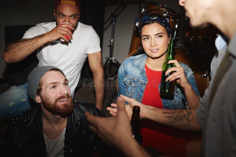 Δροσεροί νέοι που πίνουν την μπύρα στη λέσχη νύχτας στοκ εικόνες