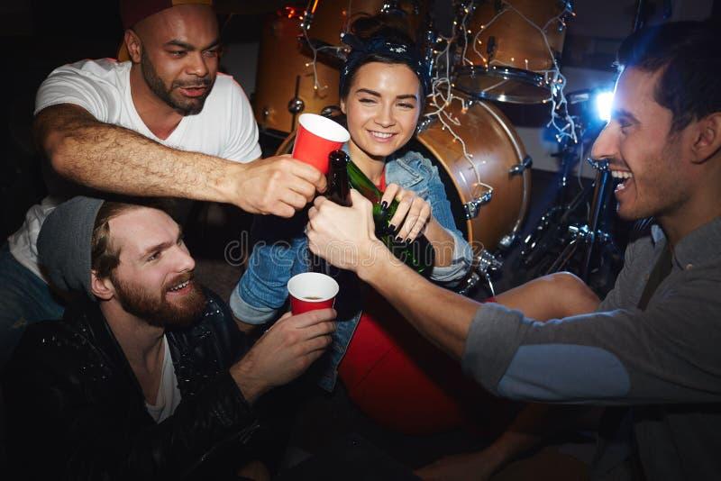 Δροσεροί νέοι που πίνουν την μπύρα στο κόμμα στο νυχτερινό κέντρο διασκέδασης στοκ εικόνες