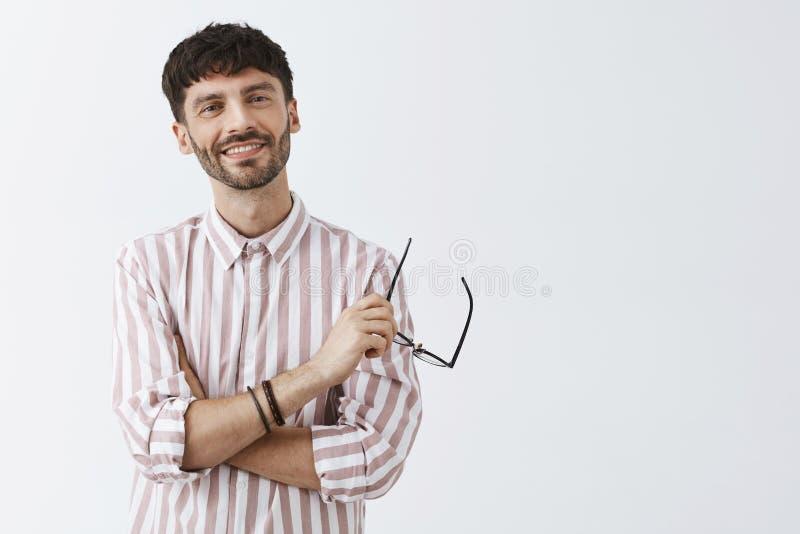Δροσερός γοητευτικός γενειοφόρος καυκάσιος τύπος με το σκοτεινό σύντομο hairstyle που διασχίζει τα χέρια στο διαθέσιμο χαμόγελο γ στοκ φωτογραφίες με δικαίωμα ελεύθερης χρήσης