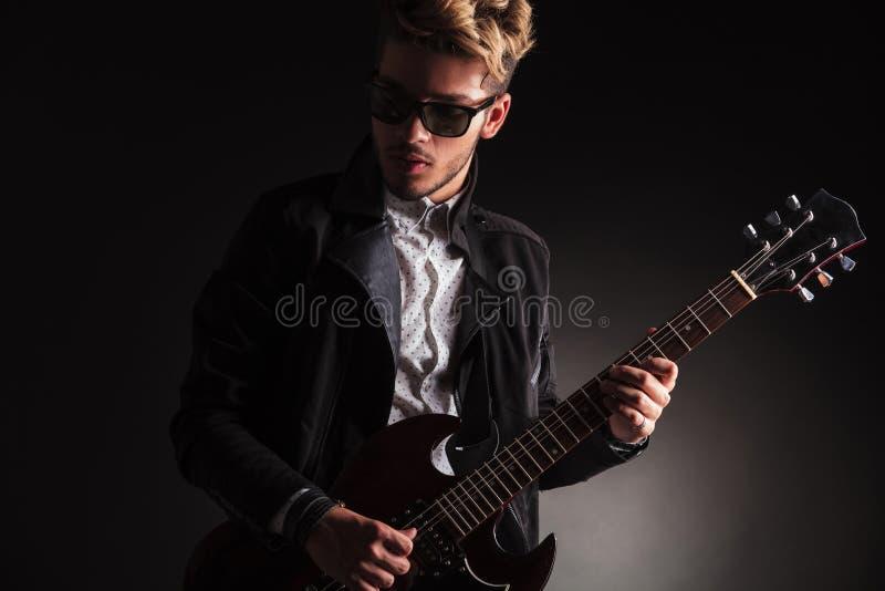 Δροσερός νέος κιθαρίστας που παίζει την ηλεκτρική κιθάρα του στοκ εικόνα
