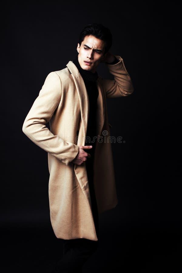Δροσερός πραγματικός νεαρός άνδρας στο παλτό στο μαύρο υπόβαθρο στοκ φωτογραφία με δικαίωμα ελεύθερης χρήσης
