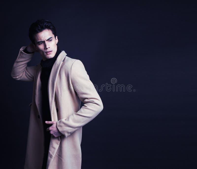 Δροσερός πραγματικός νεαρός άνδρας στο παλτό στο μαύρο υπόβαθρο στοκ εικόνα