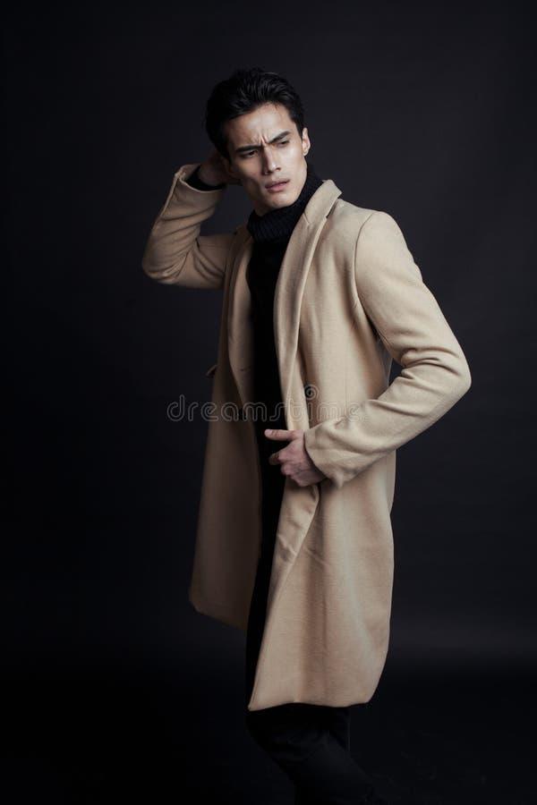 Δροσερός πραγματικός νεαρός άνδρας στο παλτό στο μαύρο υπόβαθρο στοκ φωτογραφία