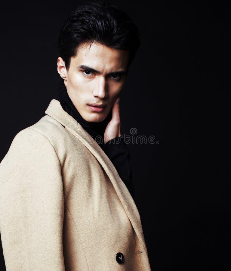 Δροσερός πραγματικός νεαρός άνδρας στο παλτό στο μαύρο υπόβαθρο στοκ φωτογραφίες