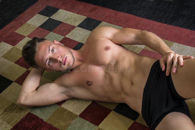 Δροσερός όμορφος νεαρός άνδρας που βάζει στο πάτωμα στοκ φωτογραφία με δικαίωμα ελεύθερης χρήσης