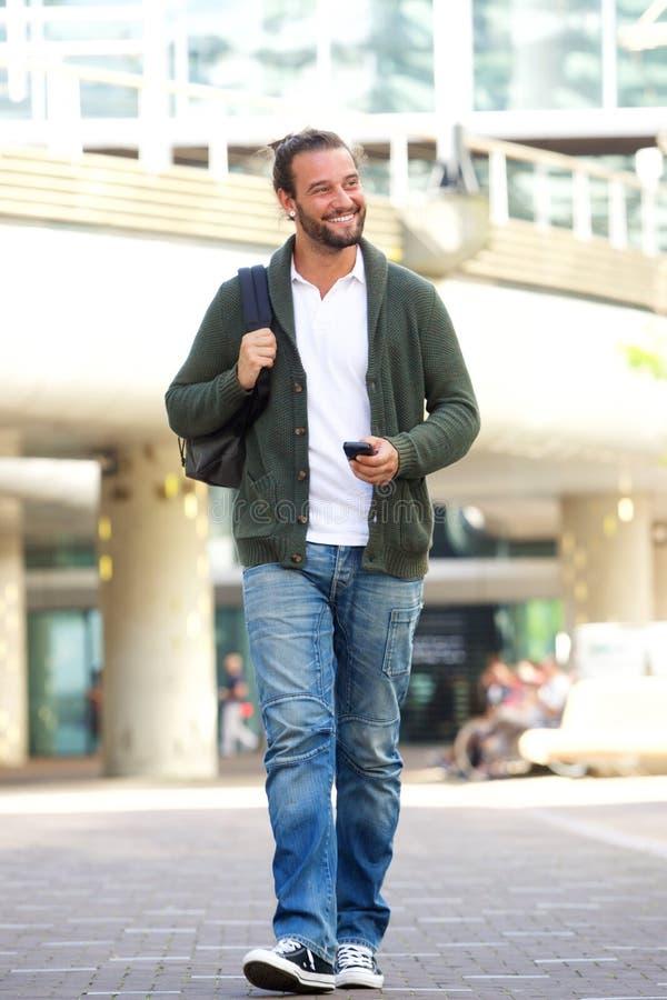 Δροσερό άτομο που περπατά με το κινητές τηλέφωνο και την τσάντα στοκ φωτογραφία με δικαίωμα ελεύθερης χρήσης