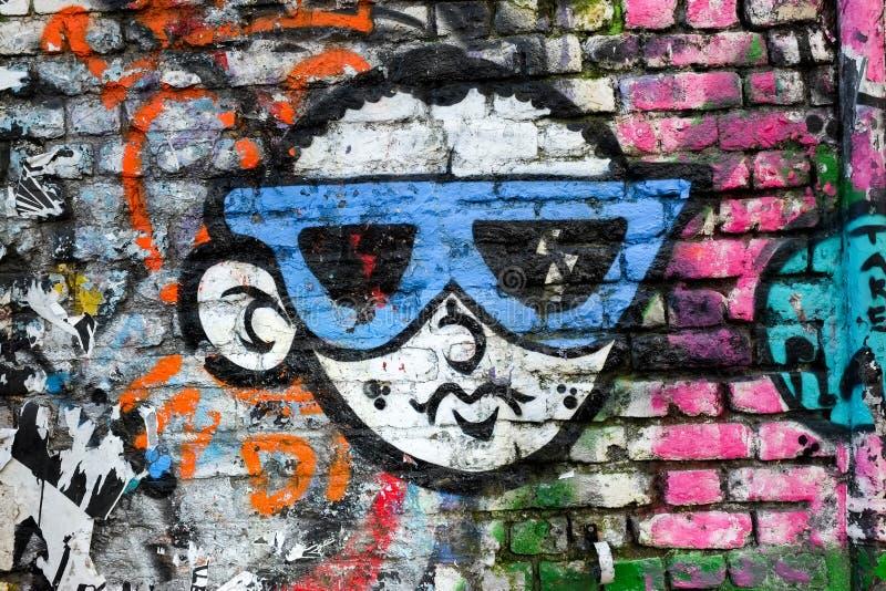 Δροσερό αγόρι που φορά τα γυαλιά ηλίου, σχέδιο γκράφιτι, Λονδίνο UK απεικόνιση αποθεμάτων