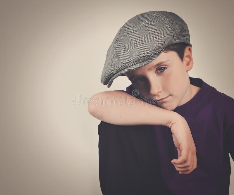 Δροσερό αναδρομικό αγόρι με το καπέλο στο υπόβαθρο στοκ εικόνα