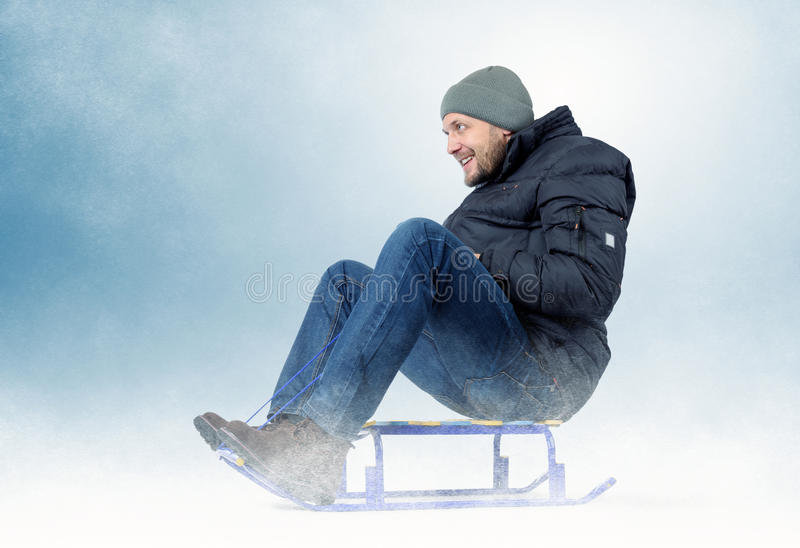 Δροσερό γενειοφόρο άτομο σε ένα έλκηθρο στο χιόνι στοκ εικόνες με δικαίωμα ελεύθερης χρήσης