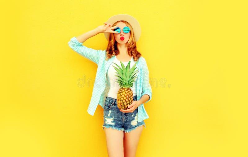 δροσερό κορίτσι με τον ανανά που φυσά τα κόκκινα χείλια που στέλνουν το γλυκό φιλί αέρα στο καπέλο θερινού αχύρου, γυαλιά ηλίου,  στοκ φωτογραφίες