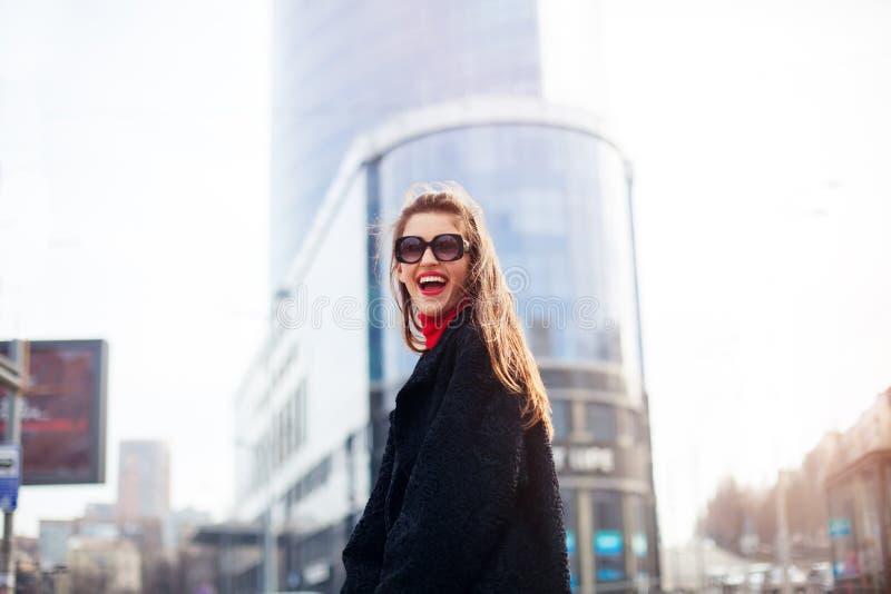Δροσερό κορίτσι με το μακροχρόνιο hairstyle και τα κόκκινα χείλια που έχουν τη διασκέδαση στην πόλη Φορά τα γυαλιά ηλίου και το χ στοκ εικόνες