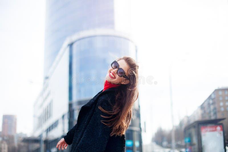 Δροσερό κορίτσι με το μακροχρόνιο hairstyle και τα κόκκινα χείλια που έχουν τη διασκέδαση στην πόλη Φορά τα γυαλιά ηλίου και το χ στοκ εικόνες με δικαίωμα ελεύθερης χρήσης