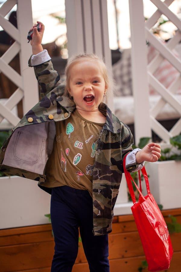 Δροσερό μοντέρνο κοριτσάκι στα περιστασιακά και στρατιωτικά ενδύματα στην οδό στοκ εικόνα
