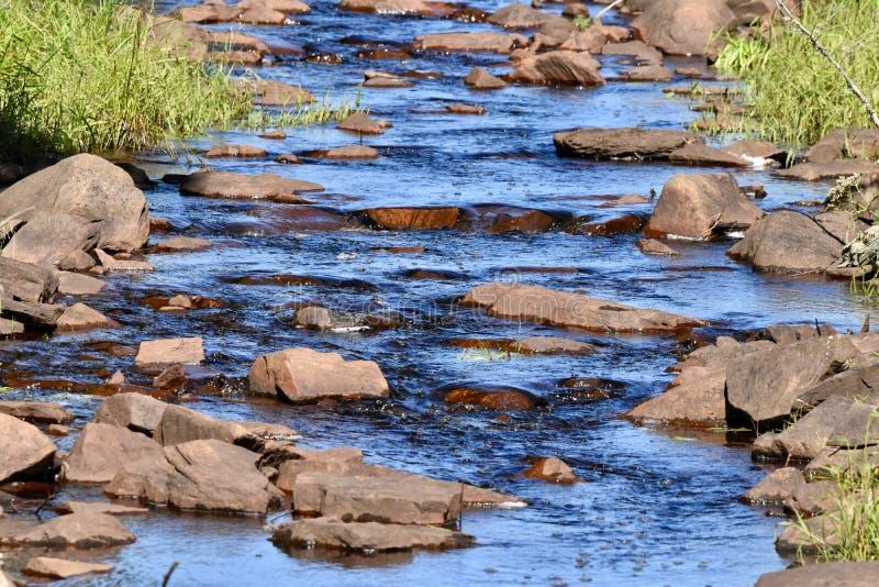 Δροσερό μπλε νερό που πέφτει απότομα ήπια κάτω από ένα ρυάκι στοκ φωτογραφία με δικαίωμα ελεύθερης χρήσης