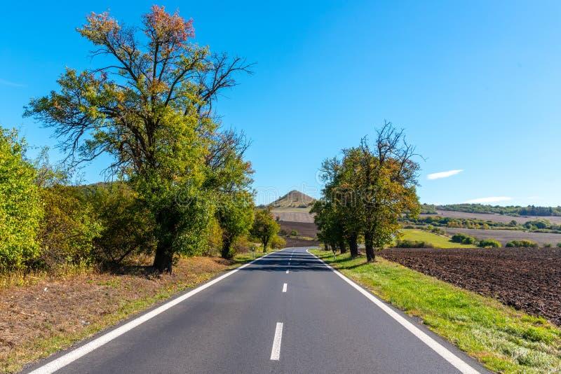 Δρόμος ασφάλτου και χαρακτηριστικός κωνικός ηφαιστειακός λόφος του κεντρικού Βοημίας Χάιλαντς την ηλιόλουστη θερινή ημέρα, Δημοκρ στοκ φωτογραφία