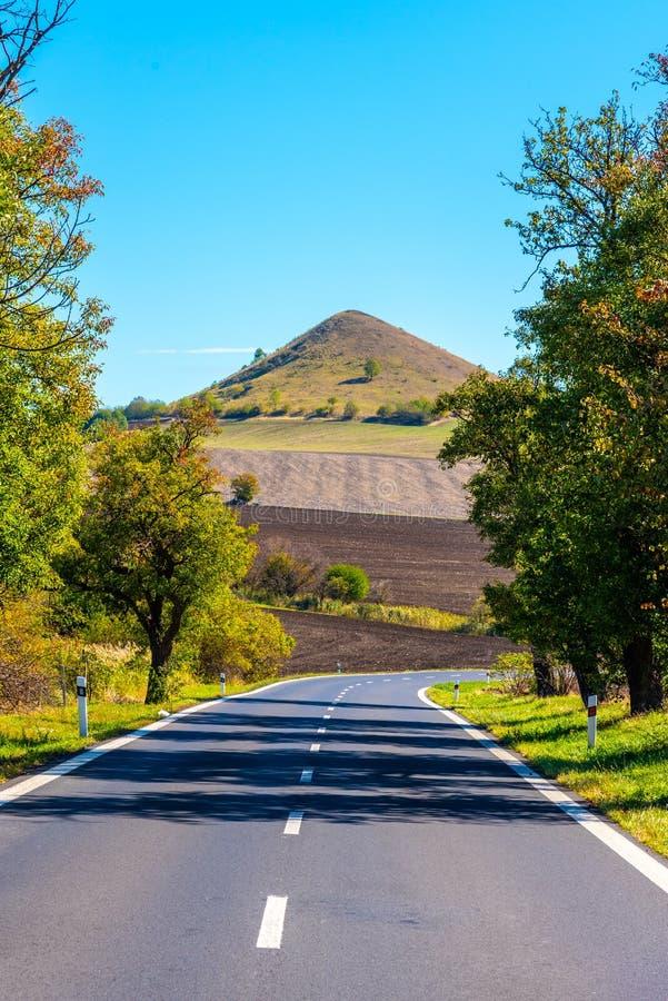 Δρόμος ασφάλτου και χαρακτηριστικός κωνικός ηφαιστειακός λόφος του κεντρικού Βοημίας Χάιλαντς την ηλιόλουστη θερινή ημέρα, Δημοκρ στοκ εικόνες