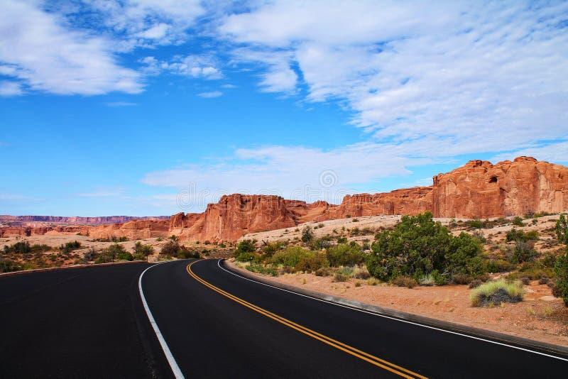 Δρόμος ασφάλτου που κάμπτει γύρω από τη γωνία με τους απότομους σχηματισμούς βράχου ερήμων στη Γιούτα στοκ φωτογραφία με δικαίωμα ελεύθερης χρήσης