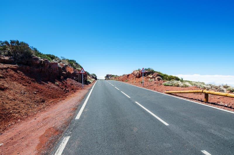 Δρόμος βουνών πέρα από τα σύννεφα Κίνδυνος σημαδιών κυκλοφορίας ` χιονιού ` στις άκρες του δρόμου Εθνικό πάρκο Teide, Tenerife, Κ στοκ φωτογραφία