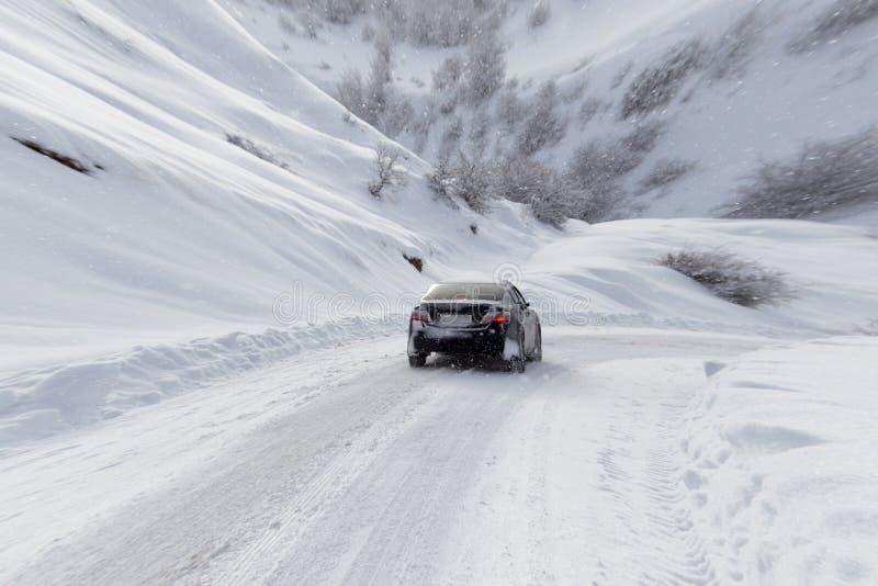 Δρόμος με ένα αυτοκίνητο το χειμώνα στα βουνά στοκ φωτογραφίες