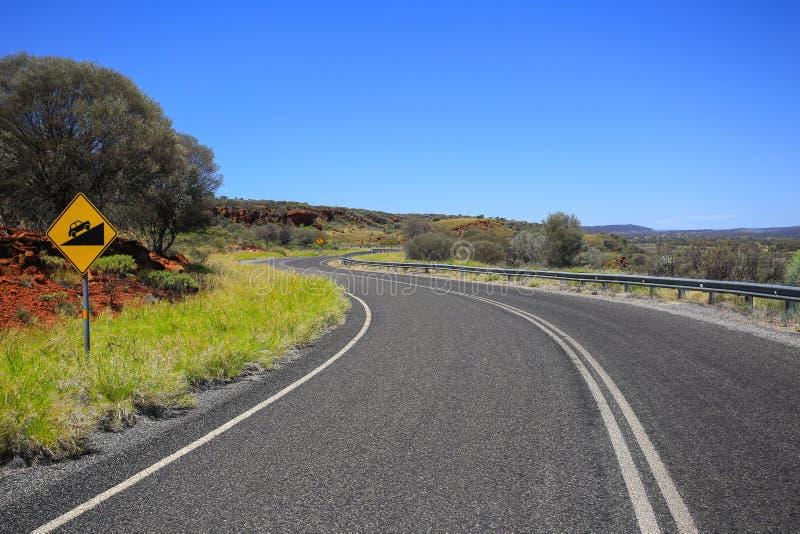 Δρόμος με πολλ'ες στροφές Κίτρινο οδικό σημάδι Προσοχή που στρίβει το δρόμο στοκ εικόνα