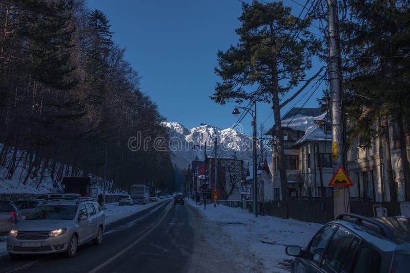 Δρόμος με τα αυτοκίνητα στη μικρή πόλη στο υπόβαθρο των χιονωδών βουνών Ρουμανία, Sinaia στοκ εικόνες με δικαίωμα ελεύθερης χρήσης
