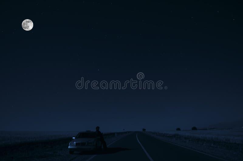 Δρόμος με το αυτοκίνητο και sillhouette του ατόμου και ένα αυτοκίνητο στην οδική πλευρά τη νύχτα κάτω από το φως φεγγαριών Αζερμπ στοκ εικόνες