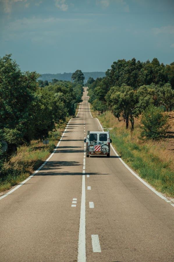 Δρόμος με το μόνο αυτοκίνητο μέσω του αγροτικών τοπίου και των δέντρων στοκ φωτογραφία